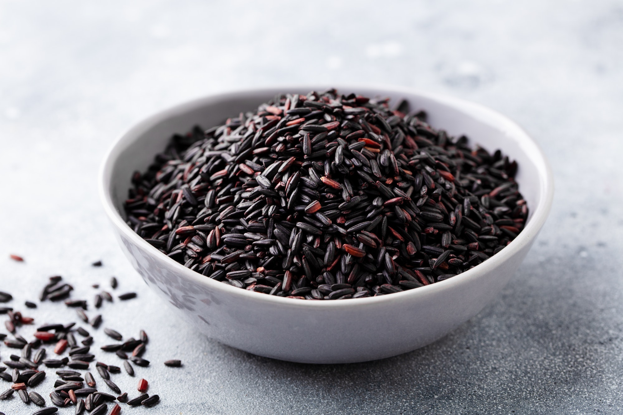 Black wild rice in a bowl. Grey stone background. Close up.